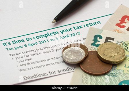 Reminder Letter that it is time to complete a tax return. On the letter is a pen and british Sterling currency - Stock Photo