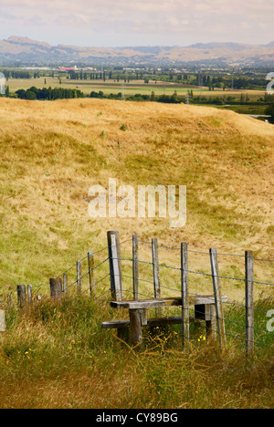 A stile over a fence in New Zealand with an open vista beyond - Stock Photo