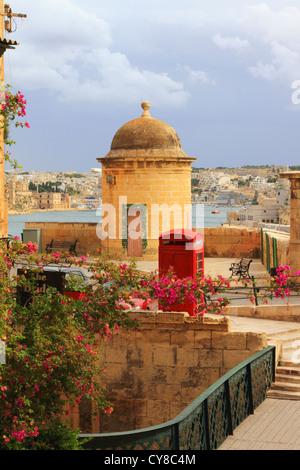 British red telephone kiosk in Valletta, Malta overlooking Port Kbir - Stock Photo