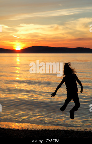 Girl leaping into the air above the setting sun, Sunset Beach, Washington Park, Anacortes, Skagit County, Washington - Stock Photo