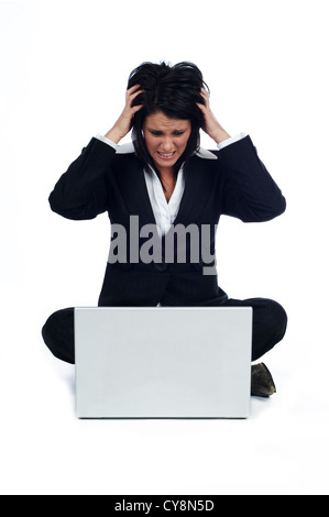 Business woman sat on the floor with a laptop stressed pulling out her hair, isolated on a white background - Stock Photo