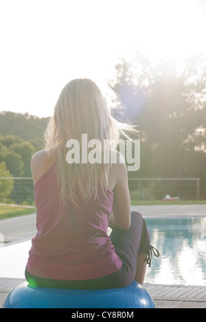 Woman sitting on fitness ball at poolside, rear view - Stock Photo