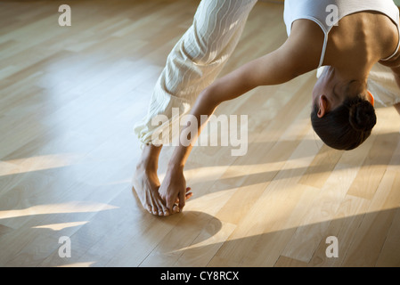woman doing yoga asana prasarita padottanasana stock photo