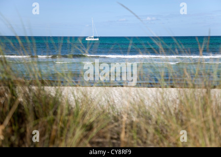 Tranquil beach scene, sail boat visible in distance - Stock Photo