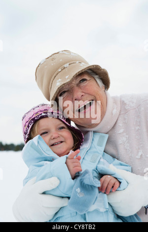 Grandmother and toddler girl embracing in snow - Stock Photo