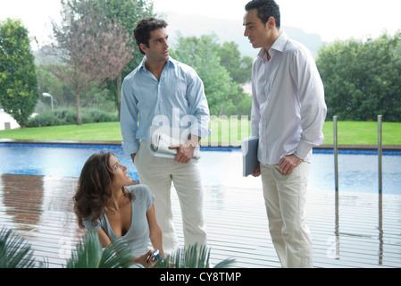 Casually dressed executives having poolside meeting - Stock Photo