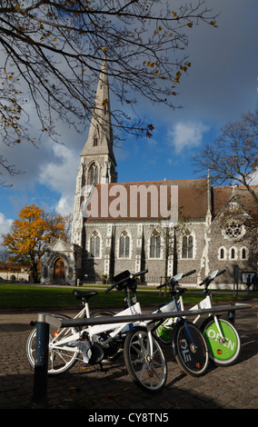 Free City Bikes in front of the Anglican St. Alban's Church, or the English Church on an autumn afternoon in Copenhagen, - Stock Photo