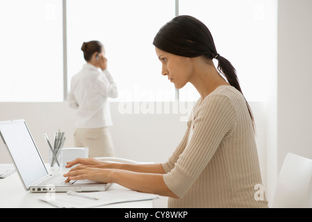 Young pregnant woman typing on laptop computer in office, backlit - Stock Photo