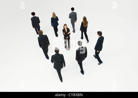 Businesswoman standing in midst of other anonymously dressed business professionals - Stock Photo