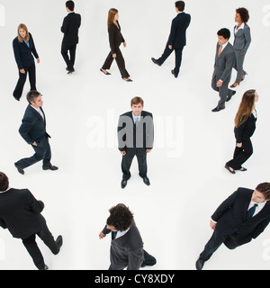 Businessman standing still in midst of other business professionals on the move - Stock Photo
