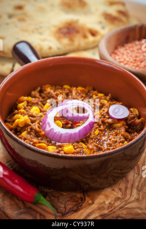 Mexican chilli con carne with red lentils and flat bread - Stock Photo