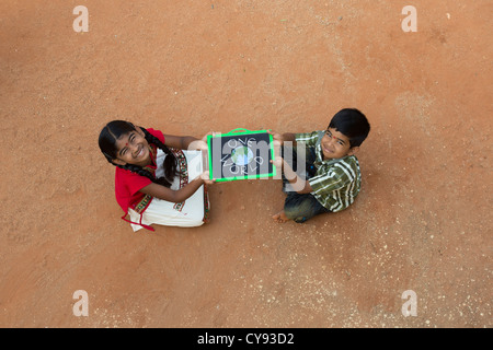 Indian village girl and boy with ONE WORLD written on a chalkboard in a rural indian village. Andhra Pradesh, India - Stock Photo