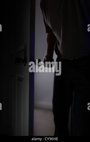 Male fist clenched entering a dark room. Model released - Stock Photo
