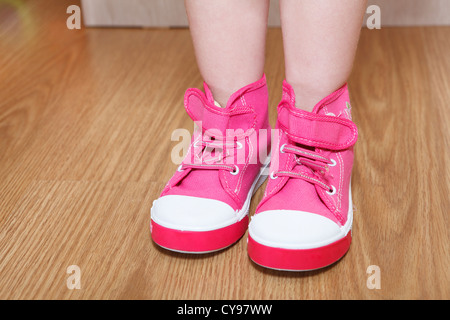 Children legs in pink shoes standing on the floor - Stock Photo