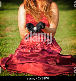 a woman in a red dress is sitting on a meadow, holding a feather in her hands - Stock Photo