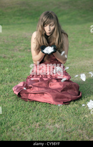 a woman in a red dress is sitting on a meadow, holding feathers in her hands - Stock Photo