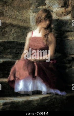 a woman in a red dress sitting on stone steps - Stock Photo