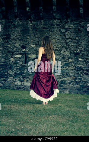 a woman in a red dress is running at a castle wall - Stock Photo