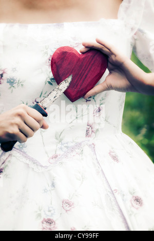 a woman in a period dress is holding a heart and a knife - Stock Photo