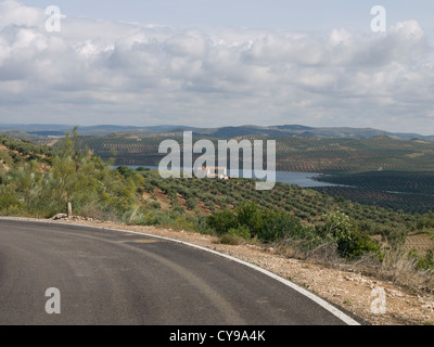 On the road in Andalusia Spain, olive groves and open landscape, a water reservoir - Stock Photo