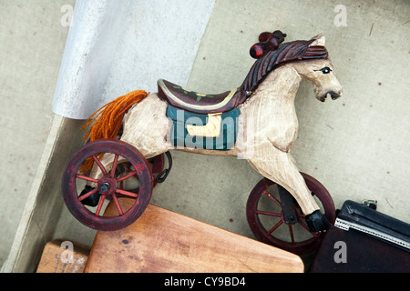 beautiful old polychrome wood miniature white hobby horse toy with orange yarn tail for sale at Hells Kitchen weekend - Stock Photo