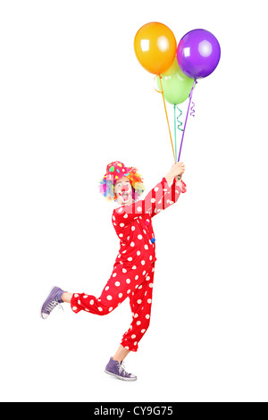 Full length portrait of a male clown holding balloons and flying isolated on white background - Stock Photo