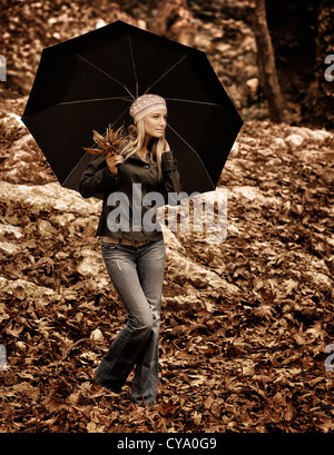 Retro style image of beautiful girl standing under black umbrella in autumnal woods, grunge and sepia effect, brown - Stock Photo