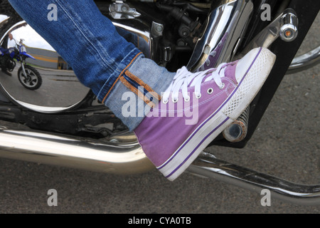 Leg of the girl on footboard of the motorcycle - Stock Photo