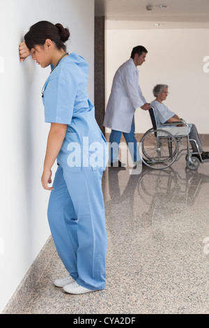 Distressed nurse standing against wall - Stock Photo
