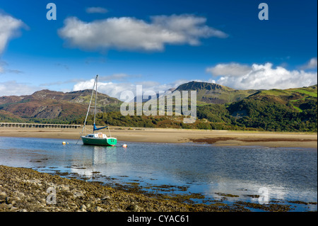 A green hulled sailing yacht is anchored in the mawddach estuary, low tide, cadair idris mountains in background, - Stock Photo