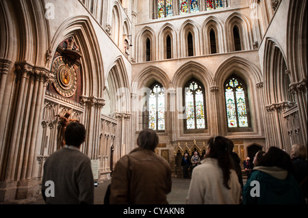 WELLS, UK - Tourists watch the famous clock of Wells Cathedral in Wells, Somerset, United Kingdom. Some of the building - Stock Photo