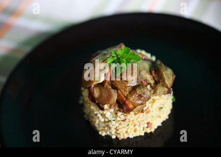 Porcini mushrooms and millet dish with parsley, food styling - Stock Photo