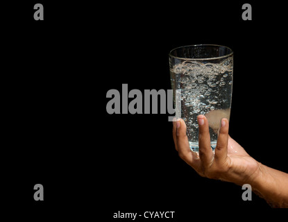 Bubbling water in a glass held by Indian girls hands - Stock Photo