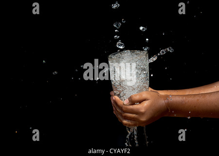 Water being poured into a glass held by Indian girls hands - Stock Photo