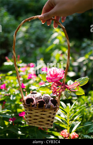 Homemade chocolates in a basket with flowers in the background.