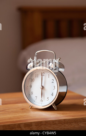 Alarm clock by bedside set at 6 AM - Stock Photo