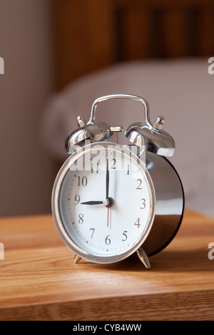 Alarm clock by bedside set at 9 AM - Stock Photo