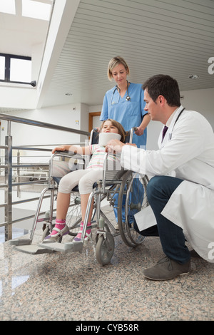 Doctor crouching next to child in wheelchair with nurse pushing it - Stock Photo