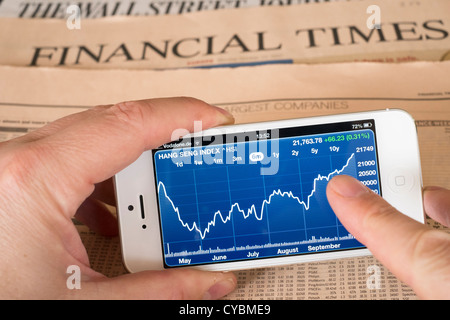 Detail of iPhone 5 smart phone screen showing financial app with stock market data - Stock Photo