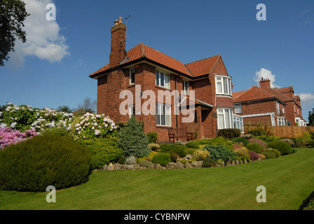 Large brick detached house in UK with grass lawn and beautiful garden and rockery - Stock Photo