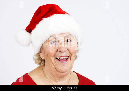 Grand-mother or elderly woman with big happy smile wearing Santa Claus hat; perfect for Christmas and seniors themes - Stock Photo