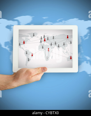 Hand showing a tablet PC displaying world map - Stock Photo