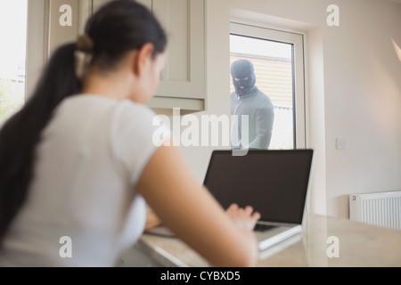 Burglar Looking At Woman Through Glass Door Stock Photo 71866540