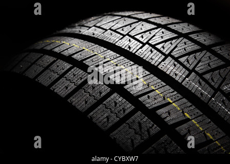 Part of brand new modern winter car tyre on a black background. Studio shot. - Stock Photo