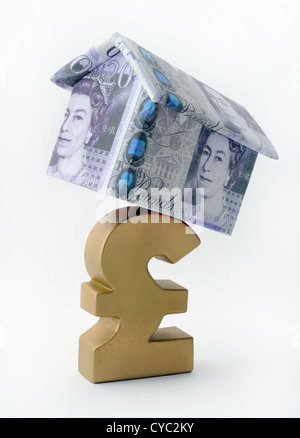 HOUSE MADE OF BRITISH CURRENCY BALANCING ON POUND SIGN RE SAVINGS MORTGAGES INCOMES WAGES THE ECONOMY RECESSION - Stock Photo