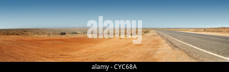 Panorama of the Australian Outback with red dirt and remote road - Stock Photo