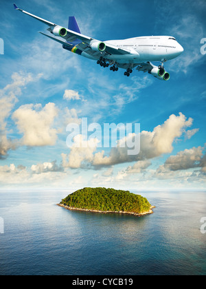 Jumbo jet over the tropical island. Vertical composition in high resolution. - Stock Photo