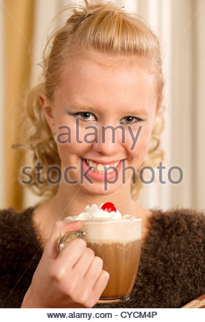 young woman holding a cup of hot chocolate smiling at the camera - Stock Photo