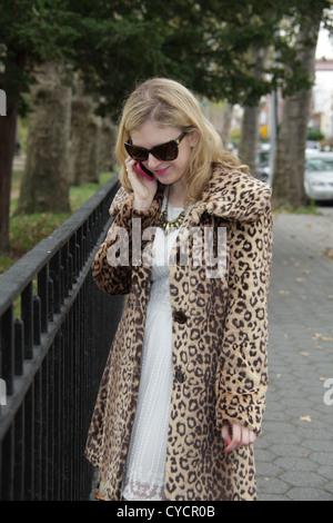 Woman in leopard print coat using Smartphone in Astoria, Queens, New York City, October 26, 2012 © Katharine Andriotis - Stock Photo