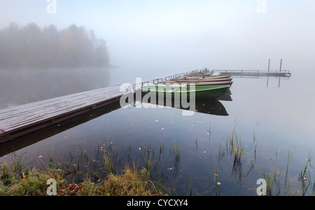 Small wooden pier with boats on lake in cold foggy morning - Stock Photo